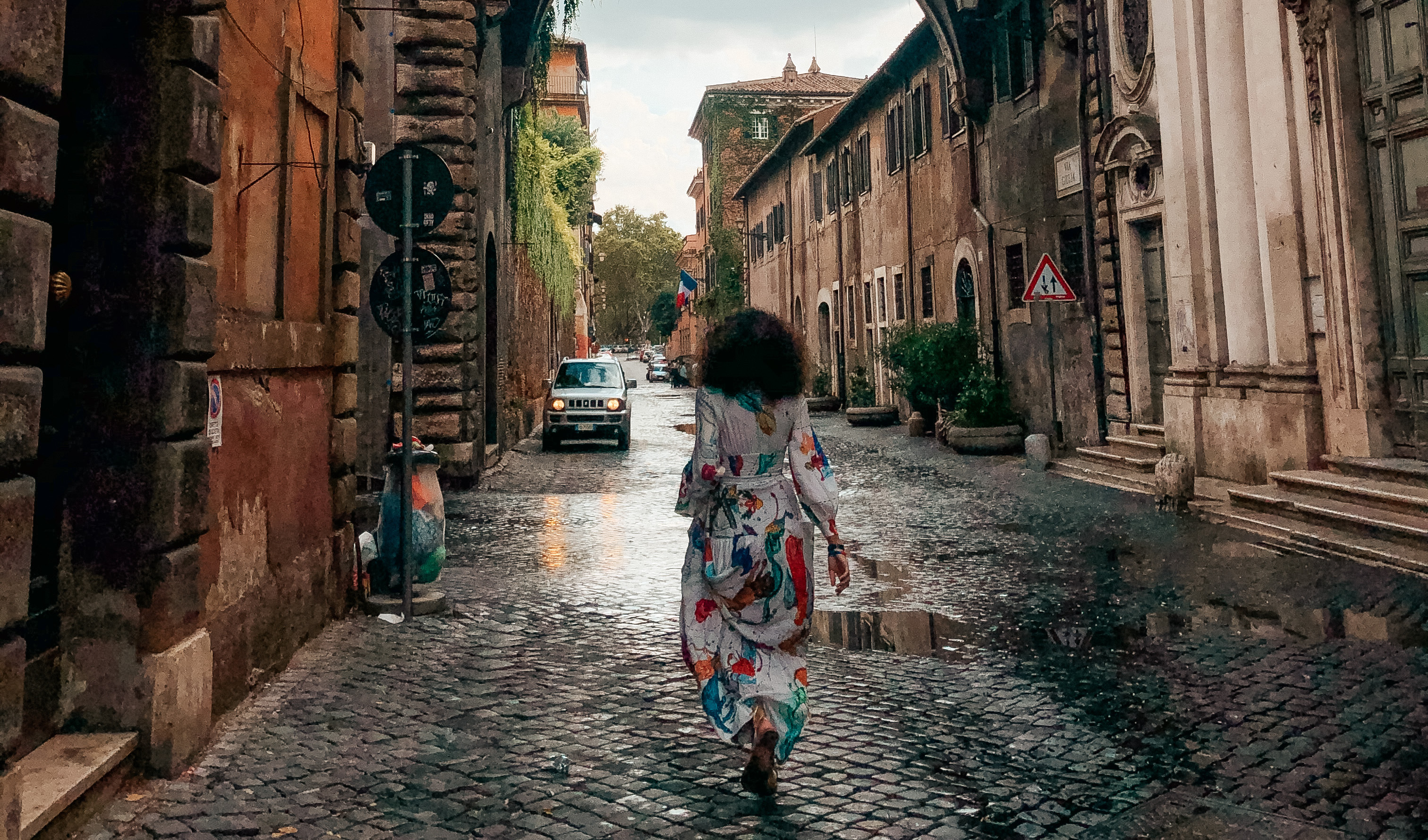 Stella walking down a raining street in Rome