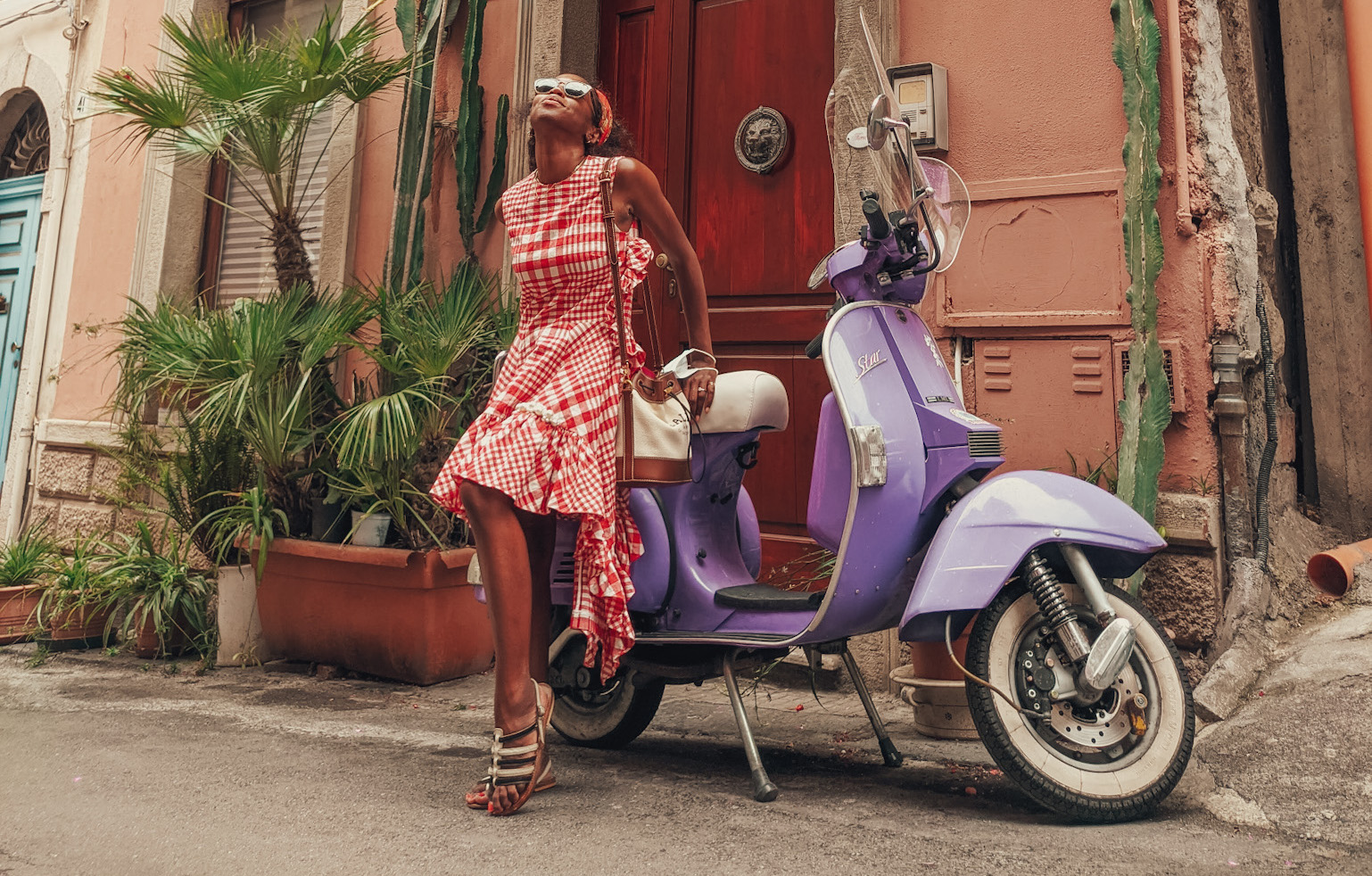 woman in front of purple Vespa in red check dress